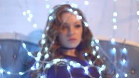 Όμορφο προκλητικό redhead κορίτσι που τυλίγεται λάμπες φωτός στις φωτεινές Χριστουγέννων φιλμ μικρού μήκους