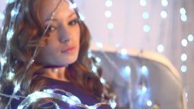 Όμορφο προκλητικό redhead κορίτσι που τυλίγεται λάμπες φωτός στις φωτεινές Χριστουγέννων απόθεμα βίντεο