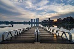 Όμορφο πρωί κοντά στην όχθη της λίμνης, το σύγχρονο κτήριο και τον ξύλινο λιμενοβραχίονα στοκ φωτογραφία με δικαίωμα ελεύθερης χρήσης