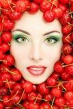 Όμορφο πρόσωπο γυναικών με το κόκκινο ώριμο φρέσκο κεράσι Στοκ Εικόνες