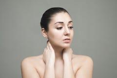 Όμορφο πρόσωπο της νέας γυναίκας με καθαρό φρέσκο στενό επάνω δερμάτων που απομονώνεται σε γκρίζο Στοκ Εικόνα