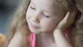 Όμορφο πρόσωπο του χαμογελώντας ξανθού κοριτσιού που διαβάζει ένα βιβλίο με το ενδιαφέρον, κινηματογράφηση σε πρώτο πλάνο φιλμ μικρού μήκους