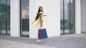 Όμορφο πρότυπο κορίτσι μετά από να ψωνίσει με τις συσκευασίες στα χέρια κίνηση αργή HD απόθεμα βίντεο