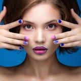 Όμορφο πρότυπο κορίτσι με το φωτεινό makeup και τη χρωματισμένη στιλβωτική ουσία καρφιών Πρόσωπο ομορφιάς Κοντά ζωηρόχρωμα καρφιά Στοκ Φωτογραφίες