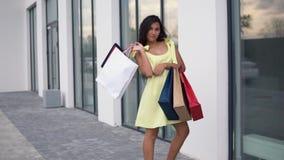 Όμορφο πρότυπο κοριτσιών σε ένα μακρύ φόρεμα μετά από να ψωνίσει με τις χρωματισμένες τσάντες στα χέρια που έχουν μια καλή διάθεσ απόθεμα βίντεο