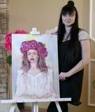 Όμορφο πρότυπο, με ένα στεφάνι των ερυθρών peonies στο κεφάλι πρότυπο κοριτσιών που χρωματίζεται στον καμβά Ο καλλιτέχνης παρουσι στοκ φωτογραφία με δικαίωμα ελεύθερης χρήσης