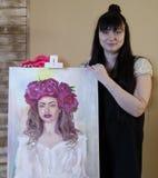 Όμορφο πρότυπο, με ένα στεφάνι των ερυθρών peonies στο κεφάλι πρότυπο κοριτσιών που χρωματίζεται στον καμβά Ο καλλιτέχνης παρουσι στοκ εικόνες