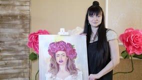 Όμορφο πρότυπο, με ένα στεφάνι των ερυθρών peonies στο κεφάλι πρότυπο κοριτσιών που χρωματίζεται στον καμβά Ο καλλιτέχνης παρουσι στοκ φωτογραφία