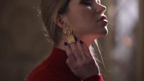 Όμορφο πρότυπο μόδας στην κόκκινη τοποθέτηση φορεμάτων με τα σκουλαρίκια, ελκυστικό κορίτσι πολυτέλειας απόθεμα βίντεο