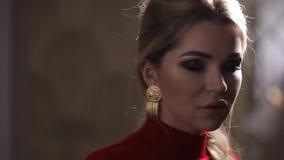 Όμορφο πρότυπο μόδας στην κόκκινη τοποθέτηση φορεμάτων με τα σκουλαρίκια απόθεμα βίντεο