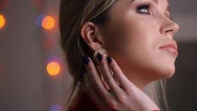 Όμορφο πρότυπο μόδας στην κόκκινη τοποθέτηση φορεμάτων σχετικά με τα σκουλαρίκια απόθεμα βίντεο