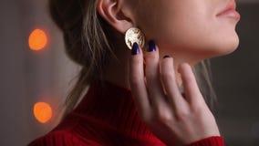 Όμορφο πρότυπο μόδας στην κόκκινη τοποθέτηση φορεμάτων σχετικά με τα σκουλαρίκια φιλμ μικρού μήκους