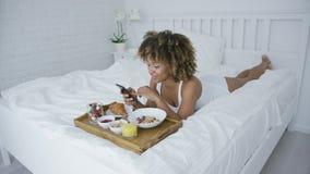 Όμορφο πρότυπο που έχει το γεύμα στο κρεβάτι απόθεμα βίντεο