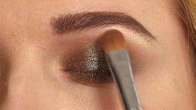 Όμορφο πρότυπο που εφαρμόζει eyeliner την κινηματογράφηση σε πρώτο πλάνο στο μάτι φιλμ μικρού μήκους