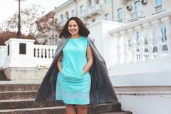 Όμορφο πρότυπο στο μπλε φόρεμα και γκρίζο παλτό στην οδό πόλεων στοκ εικόνα