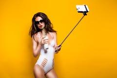 Όμορφο πρότυπο brunette στα γυαλιά ηλίου και το άσπρο monokini που παίρνει selfie με το κύτταρο στο selfiestick πίνοντας το κοκτέ Στοκ Εικόνες