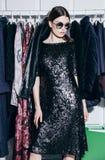 Όμορφο πρότυπο brunette clothres πλησίον στο μαύρα φόρεμα και τα γυαλιά ηλίου Στοκ Φωτογραφία