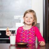 Όμορφο πόσιμο γάλα μικρών κοριτσιών με τα μπισκότα Στοκ Φωτογραφία