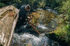 Όμορφο πόσιμο νερό κοριτσιών από τον ποταμό στο κούτσουρο μετά από το ταξίδι Ταξιδιώτης γυναικών στα θερινά περάσματα στην ξύλινη στοκ φωτογραφία