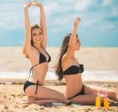 Όμορφο πόσιμο νερό νέων κοριτσιών από το boutle στην παραλία Στοκ εικόνα με δικαίωμα ελεύθερης χρήσης
