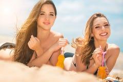 Όμορφο πόσιμο νερό νέων κοριτσιών από το boutle στην παραλία Στοκ Εικόνες