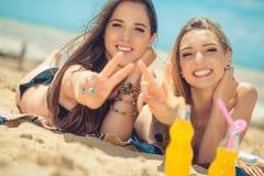 Όμορφο πόσιμο νερό νέων κοριτσιών από το boutle στην παραλία Στοκ εικόνες με δικαίωμα ελεύθερης χρήσης