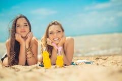 Όμορφο πόσιμο νερό νέων κοριτσιών από το boutle στην παραλία Στοκ Φωτογραφία