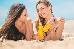 Όμορφο πόσιμο νερό νέων κοριτσιών από το boutle στην παραλία Στοκ Φωτογραφίες