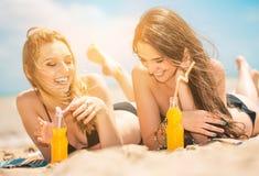 Όμορφο πόσιμο νερό νέων κοριτσιών από το boutle στην παραλία Στοκ Εικόνα