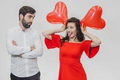 Όμορφο ρομαντικό ζεύγος που απομονώνεται στο άσπρο υπόβαθρο Μια ελκυστική νέα γυναίκα κρατά τα μπαλόνια πέρα από το κεφάλι της, α στοκ φωτογραφία με δικαίωμα ελεύθερης χρήσης
