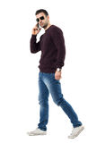 Όμορφο δροσερό περιστασιακό άτομο στο τηλέφωνο που περπατά και που εξετάζει τη κάμερα Στοκ Εικόνες