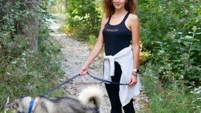 Όμορφο σγουρό κορίτσι που περπατά ένα σκυλί σε ένα λουρί απόθεμα βίντεο