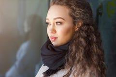 Όμορφο σγουρό κορίτσι σε ένα παλτό στην οδό Στοκ Φωτογραφία