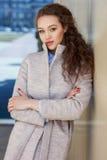 Όμορφο σγουρό κορίτσι σε ένα παλτό στην οδό Στοκ φωτογραφία με δικαίωμα ελεύθερης χρήσης