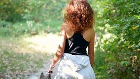 Όμορφο σγουρό μαλλιαρό κορίτσι που περπατά ένα σκυλί φιλμ μικρού μήκους