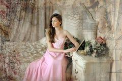 Όμορφο σκοτεινός-μαλλιαρό κορίτσι στο ρόδινο φόρεμα βραδιού στοκ εικόνες