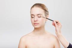 Όμορφο στενό επάνω στούντιο προσώπου γυναικών στην γκρίζα διαδικασία makeup Στοκ φωτογραφία με δικαίωμα ελεύθερης χρήσης