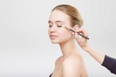 Όμορφο στενό επάνω στούντιο προσώπου γυναικών στην γκρίζα διαδικασία makeup Στοκ εικόνα με δικαίωμα ελεύθερης χρήσης