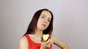όμορφο στενό κόκκινο κατανάλωσης μήλων επάνω στις νεολαίες γυναικών φιλμ μικρού μήκους