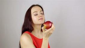 όμορφο στενό κόκκινο κατανάλωσης μήλων επάνω στις νεολαίες γυναικών απόθεμα βίντεο