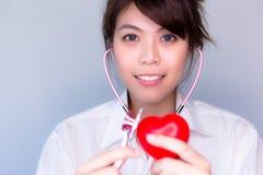 Όμορφο στηθοσκόπιο χρήσης γυναικών για τον έλεγχο της πλαστής καρδιάς στοκ φωτογραφία με δικαίωμα ελεύθερης χρήσης