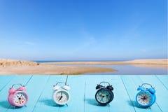 Όμορφο σύνολο νέου κλασικού ξυπνητηριού στην μπλε ξύλινη σανίδα Στοκ φωτογραφία με δικαίωμα ελεύθερης χρήσης