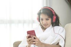 Όμορφο τηλέφωνο παιχνιδιού γυναικών στην κρεβατοκάμαρα ευτυχώς το πρωί Στοκ εικόνα με δικαίωμα ελεύθερης χρήσης