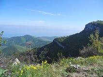 Όμορφο τοπίο βουνών με τη τοπ άποψη ένα των απόμακρων καλυμμένων δάσος κλίσεων Θάλασσα μακριά κατωτέρω στον ορίζοντα καλοκαίρι πε στοκ φωτογραφίες