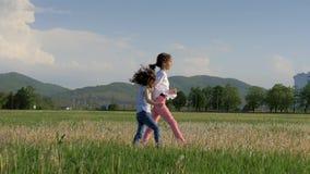 Όμορφο τοπίο δύο μικρές εύθυμες αδελφές που τρέχουν στον τομέα πικραλίδων και που γελούν απολαμβάνοντας την παιδική ηλικία ελευθε φιλμ μικρού μήκους