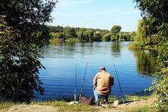 Όμορφο τοπίο με έναν ψαρά που αλιεύει στον ποταμό στοκ εικόνες