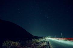 Όμορφο τοπίο νύχτας των αστεριών στη σκιαγραφία ουρανού και βουνών κοντά στο δρόμο με τα ίχνη αυτοκινήτων Δρόμος στα βουνά κάτω α Στοκ Φωτογραφία