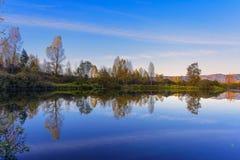 Όμορφο τοπίο πτώσης με το μπλε ουρανό που απεικονίζεται στο νερό Στοκ Εικόνες
