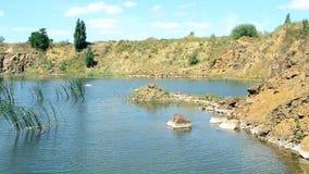 Όμορφο τοπίο της λίμνης το καλοκαίρι με τους βράχους βασαλτών, πέτρες, ήρεμο νερό απόθεμα βίντεο