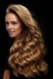 όμορφο τρίχωμα μακρύ Πρότυπο γυναικών με την ξανθή σγουρή τρίχα στοκ φωτογραφία